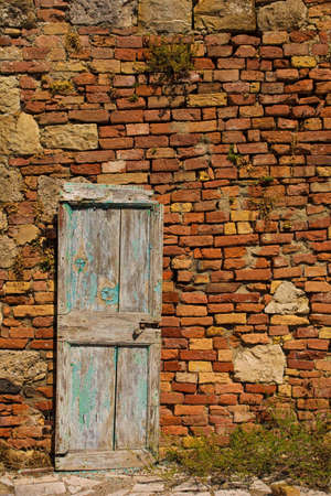 An old wooden door in a disused building in the historic medieval village of Crevole near Murlo in Siena Province, Tuscany, Italy