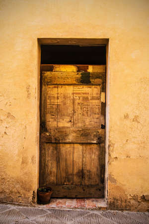 A door in the historic medieval village of San Quirico D'Orcia, Siena Province, Tuscany, Italy Stok Fotoğraf