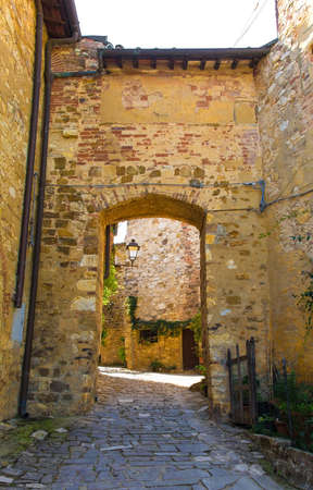 A stone archway across a quiet residential street in the historic medieval village of Montefioralle near Greve in Chianti in Florence province, Tuscany, Italy