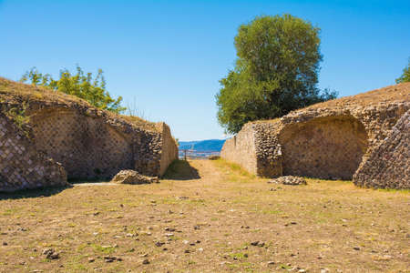 Grosseto, Italy - September 4th 2020. One of the entrances to the ruins of the amphitheatre in Roselle or Rusellae, an ancient Etruscan and Roman city in Tuscany. It stands on the northern hill of the ruins and dates from the 1st century AD