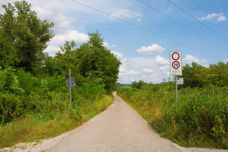 A sign on a country lane indicates that only cycles, tractors, horses and service vehicles may enter, and they must stay below 20 kph. A smaller sign indicates distances to nearby villages. In Friuli-Venezia Giulia, north east Italy