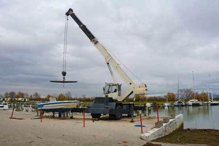 A hydraulic mobile suspended boat lift or hoist with a sling. Located in an out-of-season marina in northern Italy