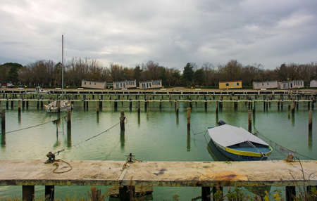 Winter at the marina of an out-of-season beach resort near Grado, Friuli-Venezia Giulia, north east Italy. Chalets can be seen in the background which have been moved to temporary positions whilst infrastructure improvement work is being carried out