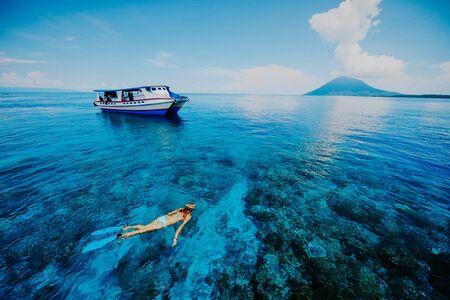 Vrouwen snorkelen in de prachtige blauwe zee aan de kant van de berg Krakatau met een scheve boot
