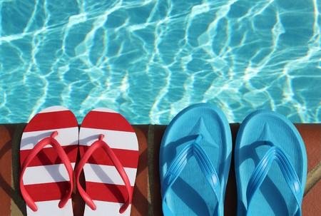 sandalias: dos pares de flops de lanzamientos en un borde de lado de la piscina