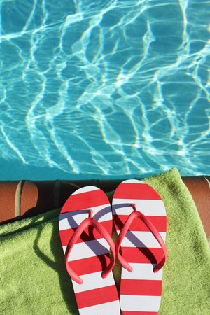 flip flops: a pair of flip flops at the edge of a swimming pool