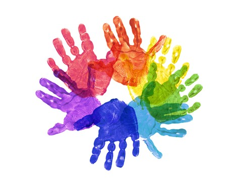 hand made: a flower made out of childrens hand prints in rainbow colours Stock Photo