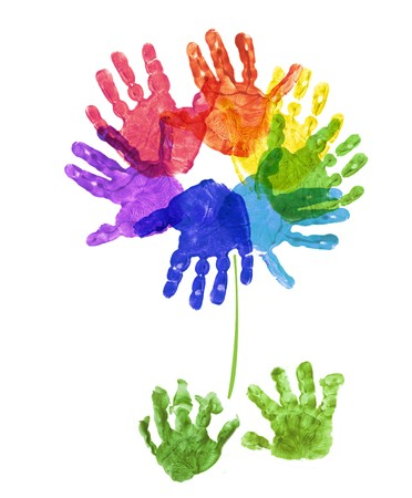 hand made: a flower made out of childs hand prints in rainbow colours on a white background Stock Photo