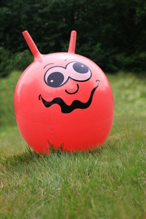 exuberance: a red space hopper on a lawn Stock Photo
