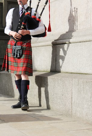 kilt: scottish man in kilt playing the bagpipes entertaining the crowd