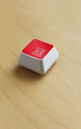 a red computer keyboard button on a wooden desk � dont panic photo