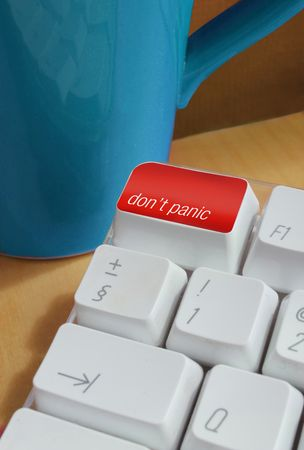 a computer keyboard with the instructions dont panic with a mug in the background photo
