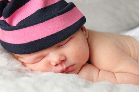 pink hat: Small new baby sleeping on a white furry blanket Stock Photo