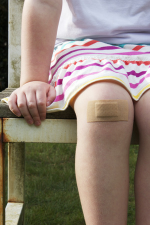 body wound: A girl sitting on a garden bench with a stripey skirt with a big plaster on her knee. Stock Photo