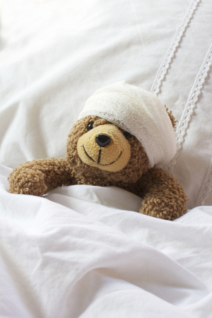 poorly: Landscape shot of a poorly teddy resting in bed