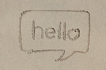 comunicación escrita: Bocadillo con la palabra hola escrito en la arena. Comunicación sencilla y gráfica. Foto de archivo