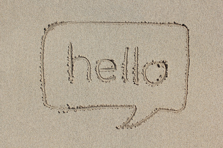 written communication: Speech bubble with the word hello written in the sand. Simple and graphic communication.