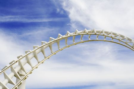 Empty roller coaster tracks against blue sky