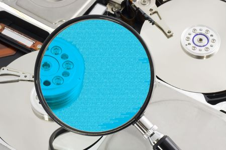 Magnifying glass over a opened hard drive depicting computer forensic Stock Photo