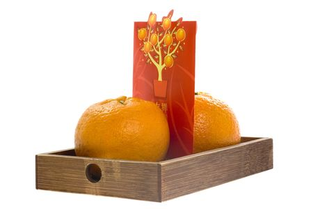 Two mandarin oranges and an ang pow on a wooden tray isolated on white background