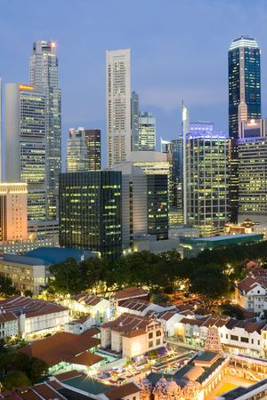 Cityscape of Singapore at dusk showing the financial district and shophouses in the foreground Stock Photo