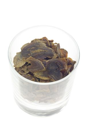 and traditional chinese medicine: Ingredient used in Traditional Chinese Medicine contained in a modern glass - Sliced red ginseng (Panax ginseng)
