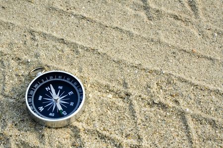 Closeup of a compass laying on a sand track