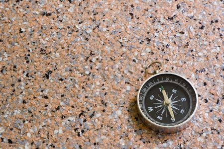 magnetic stones: Closeup of a compass laying on a rocky surface
