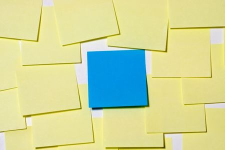 A blue note is the center of attention among yellow notes photo