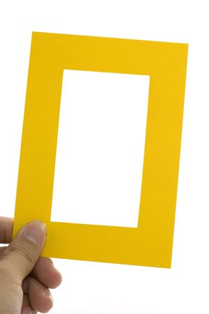 Hand holding a yellow frame isolated on white background photo