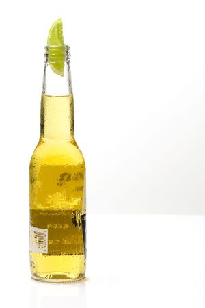 A bottle of beer with a slice of lime isolated on white background
