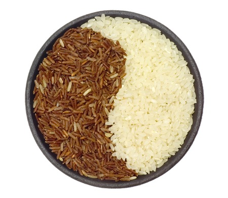 Bowl of brown and white rice forming a yin yang pattern Stock Photo