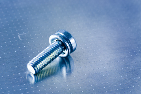 Closeup of a screw on a metal surface photo