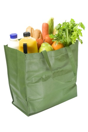 Reusable shopping bag full of groceries isolated on white background