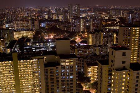 Skyline of Singapore suburbs at night showing blocks of public housing apartments Stock Photo