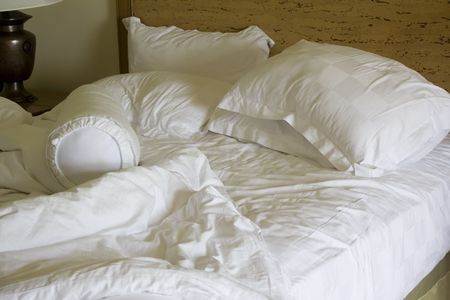 Messy unmade bed with pillow and quilt cover Stock Photo