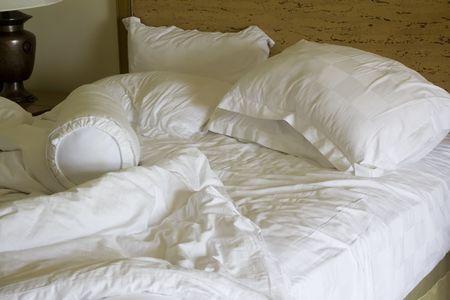edred�n: Sucias unmade cama con almohada y colcha cubierta Foto de archivo
