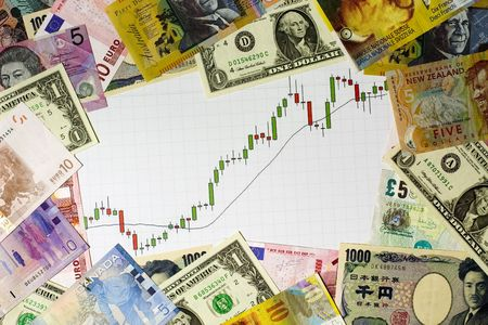 Candlestick chart showing a bull market surrounded by currencies of various countries photo