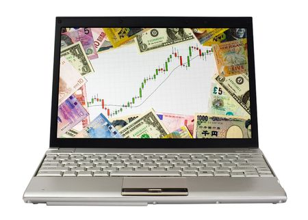 Laptop showing candlestick chart of a bull market surrounded by currencies of various countries