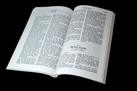 book of revelation: Open bible at the book of Revelation isolated on black background