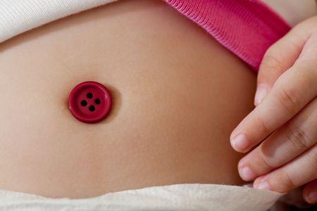 ombligo: Primer plano de un bot�n rojo que cubre el vientre de un beb� bot�n de