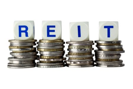 Stacks of coins with the letters REIT isolated on white background Stock Photo