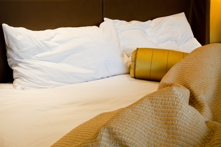 unmade: Messy luxurious bed with pillow and quilt cover