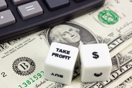 US currency with calculator and dice showing TAKE PROFIT photo