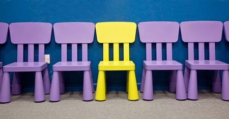conspicuous: Childrens chairs - A yellow colored one in the middle of several purple colored chairs for kids