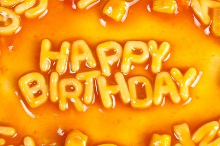 Alphabet shaped pasta forming HAPPY BIRTHDAY in tomato sauce photo