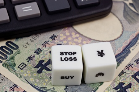 japanese currency: Japanese currency with calculator and dice showing STOP LOSS