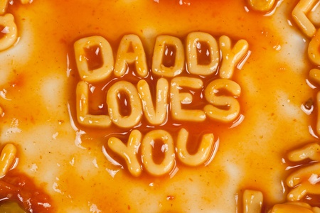 loves: Alphabet shaped pasta forming DADDY LOVES YOU in tomato sauce