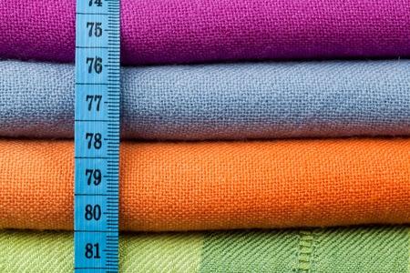 tela algodon: Pila de tela de algod�n colorido con una cinta de medici�n a trav�s de