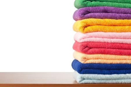 Stack of colorful microfiber towels on a table against white background photo